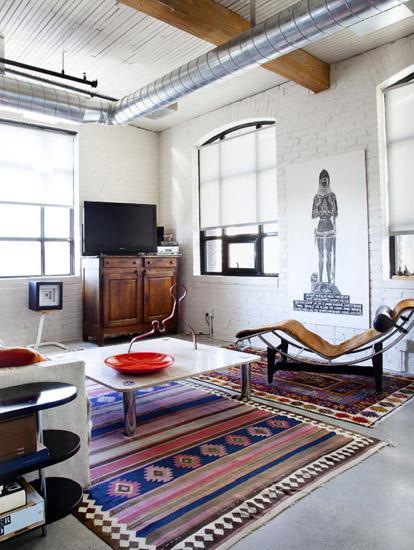 除了利用柜子和l型沙发划出客厅区域,设计师还巧妙地在天花上安上挂杆